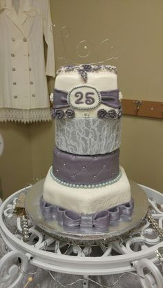 Our 25th anniversary cake! Top tier was lemon with lemon curd filling and lemon vanilla buttercream icing, the 2nd tier was faux cake, the 3rd tier was orange vanilla cake with orange vanilla icing, and the bottom tier was chocolate with strawberry vanilla icing. All decorated with buttercream fondant.
