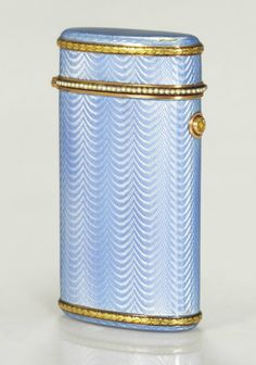 A GEMSET TWO-COLOR GOLD-MOUNTED AND GUILLOCHÉ ENAMEL CIGARETTE CASE   MARKED FABERGÉ, WITH THE WORKMASTER'S MARK OF FEODOR AFANASSIEV, ST. PETERSBURG, 1904-1908, SCRATCHED INVENTORY NUMBER 15117  Étui-form, the body enameled in translucent pale blue over a wavy guilloché ground, the ends mounted with chased and engraved laurel bands, the hinged cover set with a seed-pearl band, with colored diamond push-piece, marked throughout