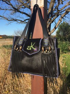 The Buckaroo Tote, in all black hair on hide, with side pockets lined in suede, lavender and lime green leather lace stitching, horse buckle fringed straps and the owners brand on the flap. Custom purses and totes from gowestdesigns.us