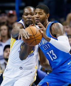 Golden State Warriors forward Kevin Durant, left, reaches for the ball held by Oklahoma City Thunder forward Paul George during the first quarter of an NBA basketball game in Oklahoma City, Wednesday, Nov. 22, 2017. (AP Photo/Sue Ogrocki)