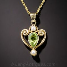 Antique Peridot and Seed Pearl Pendant. A darling, circa 1900. Elegantly hand crafted in 14 karat gold wire, scrolled at the top to create a stylized heart, wraps around a pretty pear-shaped peridot. A lustrous white seed pearl shimmers north and south of the lovely lime green gemstone. On an 18 inch chain.