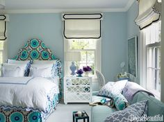 Whittaker wanted the bedroom for her client's college-age daughter to feel sophisticated, but still youthful and feminine. She upholstered the bed in Suzzani by Quadrille and dressed it in Matouk Mirasol bedding. An Ava mirrored nightstand from Worlds Away holds a Genevieve table lamp from Mitchell Gold + Bob Williams. Walls are painted Mountain Mist by Benjamin Moore.