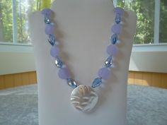 Frosted purple beads with silver tone pendant and blue teardrop crystals.