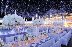 Winter wonderland wedding with lots of candlelight and high topiaries | OneWed.com