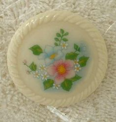 """This pin has blue and pink flowers amid daisies and green leaves. It has a 1 1/2 inch diameter and is signed """"© AVON"""" on the back. The pin is in excellent condition. For information on Avon and other"""