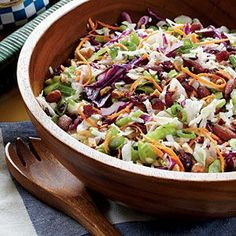 CRANBERRY-ALMOND COLESLAW  1/4 cup apple cider vinegar  2 T Dijon mustard  2 T honey  3/4 t salt  1/4 t freshly ground pepper  1/4 cup canola oil  2 (10-oz.) pkgs shredded coleslaw mix  1 cup chopped, smoked almonds  3/4 cup sweetened dried cranberries  4 green onions, sliced  2 celery ribs, sliced.