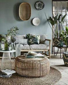 Salon vert à l'ambiance tropicale, table basse en rotin et canapé en bois
