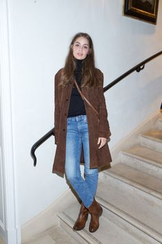 Jeans with a black turtleneck, suede coat, and a crossbody bag.