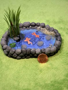 This Miniature Pond is made of polymer clay, hand painted with acrylic paint and then sealed with a waterproof sealer. Then goes in the small stones, bits of moss and lichen, artificial plants, koi fish, resin frog and finally the resin water. It can be placed into the dirt to look like it is in ground or be placed on top, either way, this pond will fit in any miniature garden scene or even the backyard of a dollhouse. This listing is for the MINIATURE POND ONLY and measures 4 1/2 x 3 1/8…
