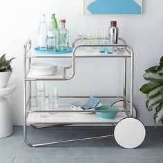 Inspired by German Bauhaus design of the 1920s and '30s, the Josef Bar Cart's minimalist profile is crafted from curved metal and white lacquer. Oversized back wheels make it easy to move wherever the party goes.