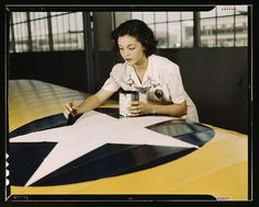 """Mrs. McElroy, a civil service employee at the Naval Air Base, Corpus Christi, Texas, paints the American insignia on airplane wings."" August 1942."