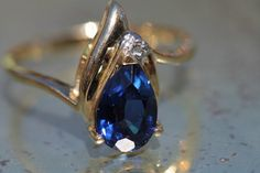 Vintage solid 10k yellow gold ring that is set with a 1.5 carat pear shaped blue sapphire and a genuine 1 point diamond.  The sapphire tests as
