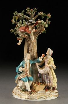 """A MEISSEN GERMAN PORCELAIN FIGURAL GROUP OF APPLE PICKERS, CIRCA 1900. Depicting a couple with young children eating apples while another picks apples from above, incised """"2229"""" and with blue crossed pommeled swords under glaze, some losses. Height 10.5 inches (26.5 cm)."""