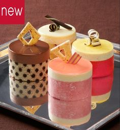 "Petits Gâteau, French for ""small cake"". These dessert cakes are constructed with layers of sponge cake and mousse. These include a crèmeux interior with a decadent glace on top. This collection includes the perfect mix of fruit and chocolate inspired flavor profiles.  Milk Chocolate Raspberry, Tropical Vanilla, luxurious White Chocolate Raspberry and refreshing Lemon Strawberry."
