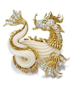 A coral, diamond, and emerald brooch, Van Cleef & Arpels designed as a carved white coral and textured gold dragon, enhanced by pavé-set diamond detail and a circular-cut emerald eye; estimated total diamond weight: 1.60 carats; mounted in eighteen karat gold and platinum.