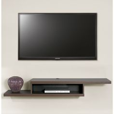 This wall mounted TV console has a modern flair with the appearance of a floating shelf in an asymetrical design that will add a modern touch to any home decor.