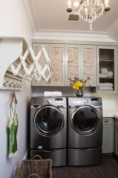 French laundry room features a Paris flea market chandelier illuminating gray cabinets fitted with French script doors suspended over a silver front load washer and dryer.