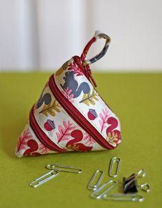 Zip around coin purse.  Tutorial here:  http://www.craftpassion.com/2011/07/zip-itself-coin-purse-tutorial.html