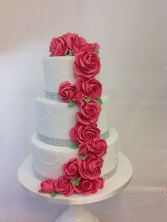 Elegant 3 tier wedding cake with diamanté border and piped pearls. Bright pink rose cascade. Wedding cakes London, Hertfordshire, Essex and Kent.