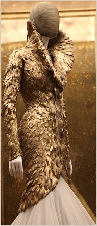 An ensemble with a coat of duck featherspainted gold and a skirt of silk tulleembroidered with gold threads.