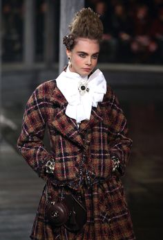 """At Chanel's Pre-Fall '13 extravaganza near Edinburgh, Scotland, Cara Delevingne wore leather mini-bags modeled after """"sporrans,"""" an important part of traditional Scottish Highland dress."""