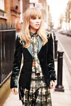 Suki Waterhouse wears Salvatore Ferragamo velvet blazer and silk blouse, skirt, and tie; crocodile belt.