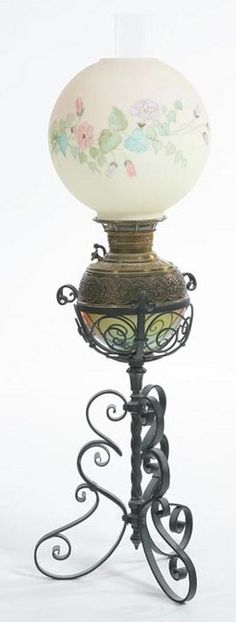 lighting, America, An unattributed piano lamp having a scrolling wrought iron base with a brass font and floral hand-painted shade. Circa 1876-1925