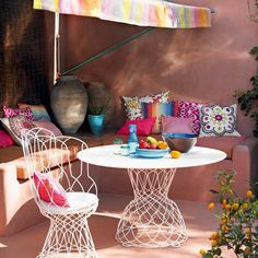 A dominant palette of pinks, from salmon to cerise, helps to unify patterned and plain cushions in this laid-back alfresco dining area. Painted stone walls give the space a sunny Mexican-feel.