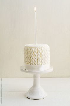 White winter birthday cake with knitted pattern made of fondant on a cake stand