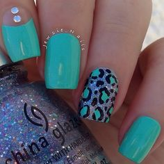 A turquoise blue themed leopard nail art design. The turquoise polish dominates the background of the nail art as well as the leopard prints as…