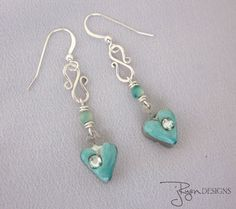 These handmade, one of a kind (OOAK) earrings feature dainty soldered heart charms in a silver metal filled with apoxie clay that has been painted a
