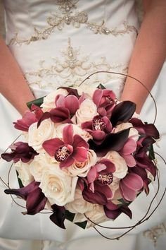 pretty wine-colored bouquet / gems centered on roses and orchids with delicate…