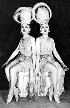 The Dolly Sisters: Roszika (Rosie) and Janszieka (Jenny) Deutsch. Any photo you find of them you will quickly find that half the time the photo is credited to Sisters G. Both pairs of twins performed during the 20s, both pairs were flamboyant flappers with dark bobs and bangs. Good luck!