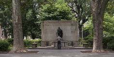 Color photo showing a solitary man standing with his back to the camera in front of the statue of George Washington at that Tomb of the Unknown Revolutionary War Soldier.  The man looks down at the tomb near his feet.