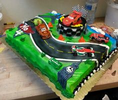 Cars 2 themed sheet cake I made for a friend. She brought in 3 of the cars and I used McQueen and Mator from the cars kit from decopac. I piped on Big Ben and the Eiffel Tower (with London and Paris signs), made one of the cars look like it skid off the road with airbrushed and piped dirt by the wheels and put little tires as the border on both short sides! I had so much fun :)