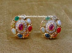 The unique combination of diamonds and precious navaratna gemstones in oval shaped earrings Pair of stud type earrings bezel set with uncut navratna stones gehna chennai Gold Bangles Design, Gold Earrings Designs, Gold Jewellery Design, Diamond Earrings Indian, Diamond Earing, Diamond Jewellery, Diamond Studs, Pendant Jewelry, Stone Jewelry