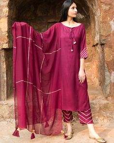 Shop online Wine straight kurta set with dupatta This is the deep wine shade straight kurta with boat neck and front dori, sleeves teamed with high ankle pants enhanced with golden gotta and georgette dupatta. Stylish Dress Designs, Stylish Dresses For Girls, Designs For Dresses, Dress Neck Designs, Simple Dresses, Sleeve Designs, Silk Kurti Designs, Kurta Designs Women, Kurti Designs Party Wear