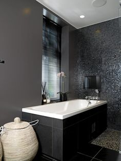 På dette maskuline badet er det brukt flere ulike typer fliser. På gulvet og rundt badekaret er det lagt store svarte fliser, mens det inntil veggen og mot dusjen er lagt brune mosaikkfliser. Den ene veggen har også fått mosaikkfliser, men her er det valgt svarte. Den andre veggen er malt i en mørk gråfarge.