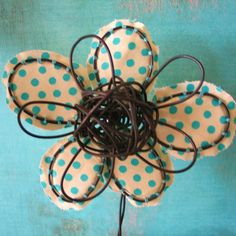 Super sweet and super cute- this polka dotted bloom is one of a kind and will breathe the freshness of nature into your decor. Its small enough to fit on a desk but will make a big impact in any cube. This flower was hand formed of 16-gauge steel wire and then I hand stitched fabric to each petal. The cream and blue polka dotted fabric is one of my faves from Moda. The base of this sculpture is a recycled cork from one of my favorite Italian Restaurants. I love this bloom and hope you do…
