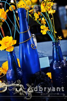 Whimsical Blue bottles with wire wrap and paper flowers accented with yellow flowers designed by Intrigue ( www.intrigue-designs.com )of Annapolis, MD. Photographed by D.Bryant Photography