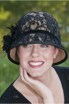 A lace embellished hat with a feathery side bow