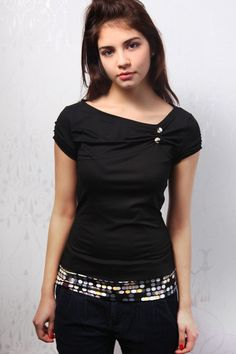 this black top is out of a comfortable to wear jersey and is shirred asymmetrical at the neckline and decorated with 2 fabric covered buttons.  hem is
