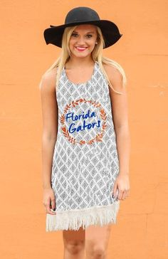 Step out in this lightweight and flowy silhouette with a slight crinkle texture and light grey geo-print pattern that is perfect for effortless layering. Wear as a tunic or tank dress, featuring cotton tassel hemline. Embellishment features glitter and matte print.   Color: Grey & White  (60% Cotton /40% Polyester) *Model wearing size XS