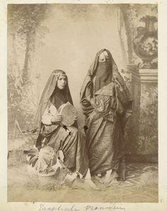 Anonymous | Studioportret van twee gesluierde vrouwen, Anonymous, c. 1890 - c. 1910 | De linker vrouw heeft een tamboerijn in de hand, de rechter vrouw draagt een sluier over haar gezicht.