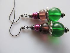 Oorbellen Hedwig matglas in groen en paars met een glasparel in fuchsia roze en tinnen kralenkap. Rest blackplated