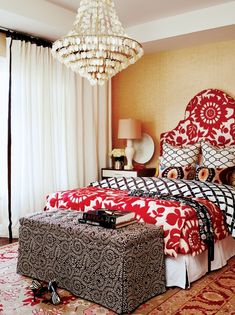 Chic, eclectic bedroom with gold grasscloth wallpaper, white & red headboard & matching blanket, white & brown lattice duvet, red & yellow wool rug, damask skirted ottoman bench, white curtains with black velvet ribbon trim and capiz chandelier.