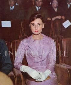 """The actressAudrey Hepburn photographed at the Teatro Sistina, on Via Sistina, in Rome (Italy), during the premiere of the movie """"Sayonara"""", on March 27, 1958.Audrey was wearing:Cocktail ensemble: Givenchy (of brocade satin in a shade of light magenta, a cropped blazer, closed by the detail of a ribbon in the same tissue, sleeves with a height above the wrists, and a sleeveless dress with length below the knees, both pieces lined with silk crepe, of his haute couture collection for the…"""