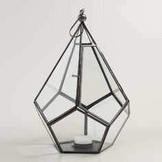 Faceted glass panels set in antique zinc-finished metal give our prism-like lantern a dimensional, contemporary appeal. Display on a tabletop or hang with a tealight inside to illuminate your space with a warm glow. I would opt for a solar light rather then a flameless led.