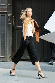 Karlie Kloss steps out in a white flowy cami tucked in black wide-leg culottes and tied altogether with a pair of classic strapped heels.