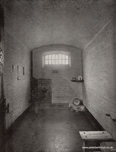 Victorian prison cell in Newgate, 1890's. We can see the water tank and basin with bedding in the corner. The shelf includes items such as a Bible, plate and a mug
